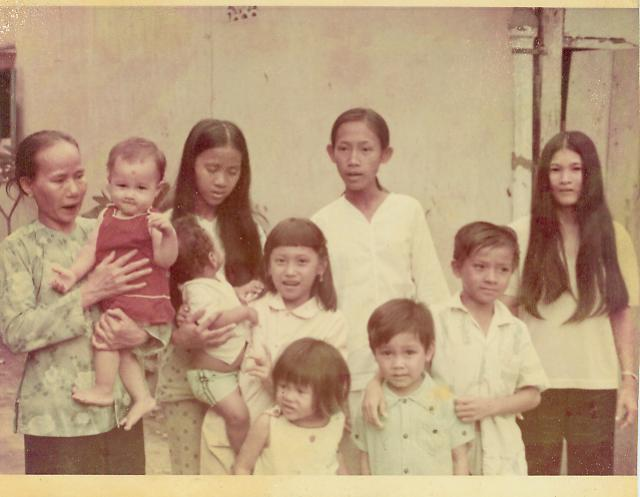 A family photo before Maaswinkel (the baby on the left) was given up for adoption. His birth mother is the woman on the right with the long hair. His older biological sister is the girl in the front facing left.