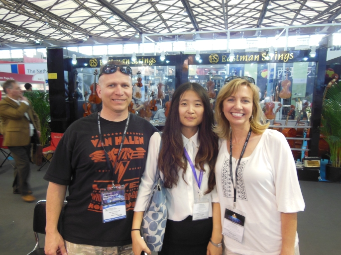 "Every year Dan and Ricia attend the ""Music China"" trade show in Shanghai where they secure instruments for their northern Virginia business, KBI Music Shoppe. The experience, which came to them after adopting their daughter Olivia from China, has resulted in a growing livelihood and new friendships, including one with their interpreter Yu (center)."